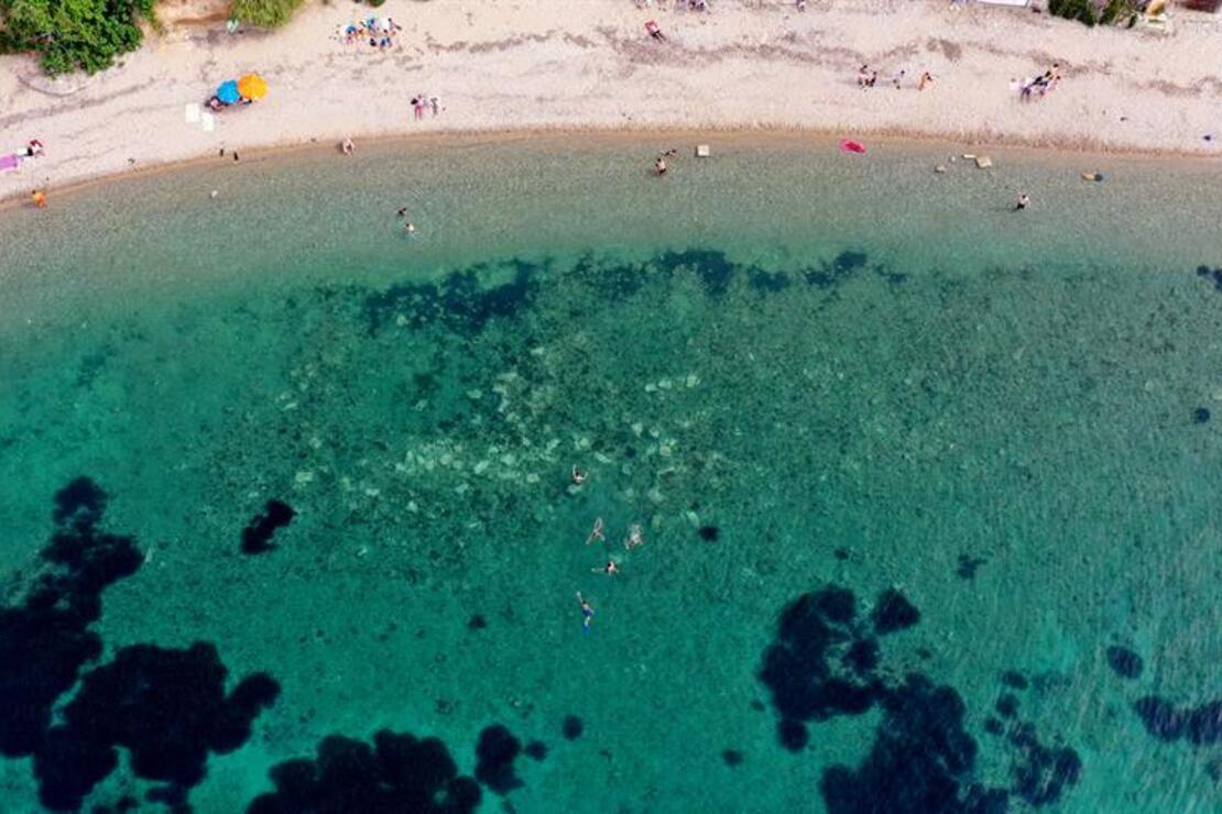Kuşadası'nda denize sosyal mesafe kurallarına uyularak giriliyor
