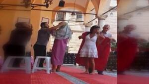 Camiyi ziyarete gelen turistleri erkek görevliler giydiriyor