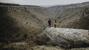 Kanyon üzerindeki taş terasta heyecan dolu poz