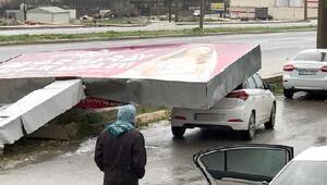 Reklam tabelası fırtınada otomobilin üzerine devrildi