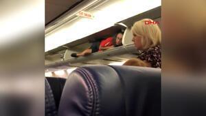 Kabin görevlisi, uçaktaki bagaj bölümüne tırmandı