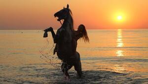 Turistler at üstünde plaj turu yapıp, gün doğumunu izliyor