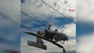 Uçak elektrik tellerinde asılı kaldı, pilot kanada oturup kurtarılmayı bekledi