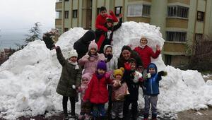 Çocuklar kamyonla taşınan karda eğlendi