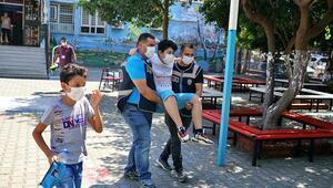Ayağı kırık öğrenci polislerin kucağında sınava gireceği sınıfa götürüldü