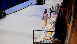 Kucağında çocukla hırsızlık yaptığı anlar kamerada