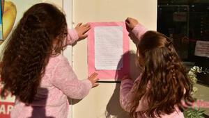 İki kardeş okula gidebilmek için sokaklara koronavirüs bilgi afişleri asıyor