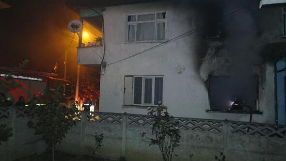 Yangın çıkan evin önündeki korkan kediyi kucaklayarak sevdi