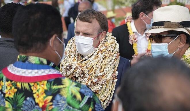 Fransa Cumhurbaşkanı Macron boynuna takılan çiçekler yüzünden hem günün adamı hem de alay konusu oldu