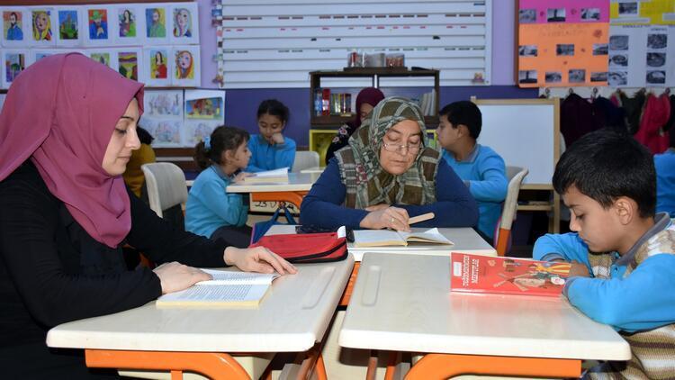 Ev ortamına dönüştürülen sınıfta velileriyle kitap okuyorlar