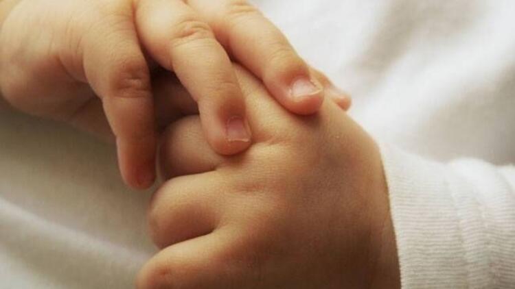 Küvezde el ele tutuşan ikiz bebekler
