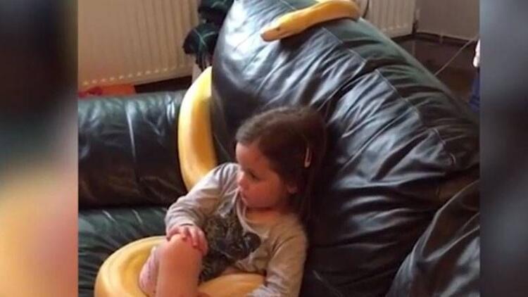 Pitona sarılıp televizyon izleyen küçük kız!
