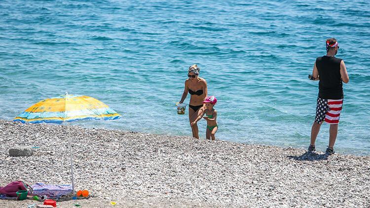 Antalya'da turistlerin boş sahilde denize keyfi