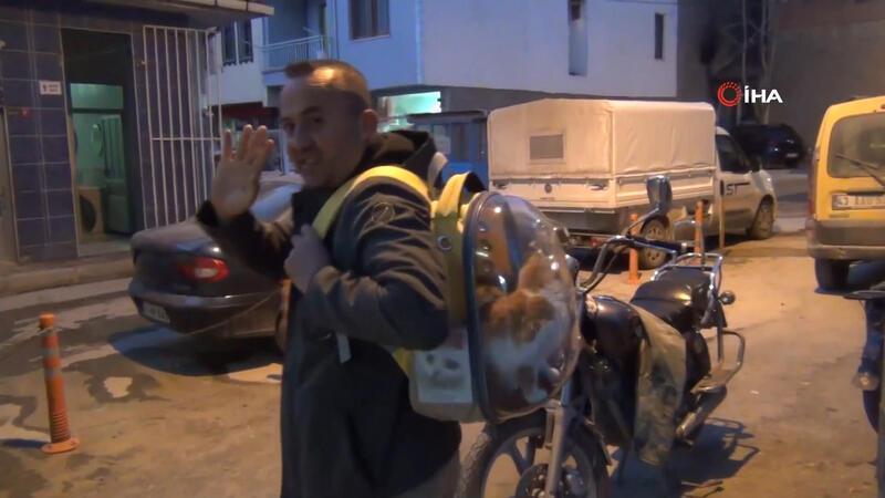 Sahiplendiği kediyi sırt çantasında gezdiriyor.