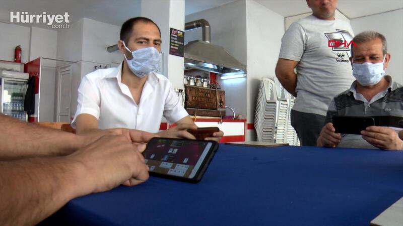 Koronavirüs yüzünden kahvehanede cep telefonuyla okey oynadılar