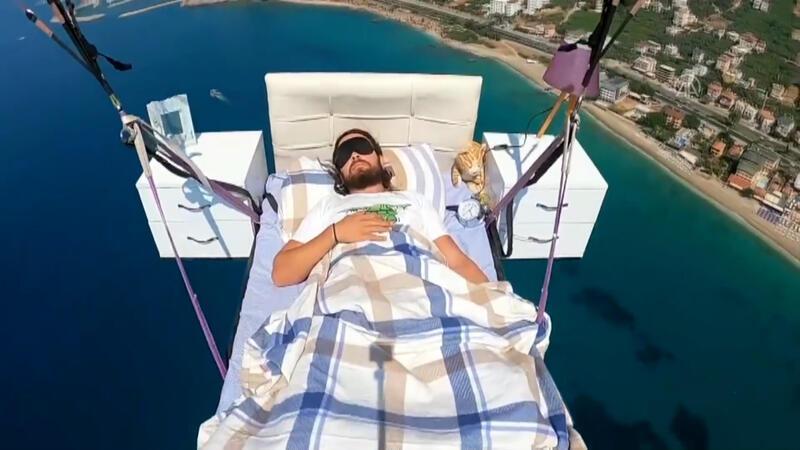Yamaç paraşütüne bağlanan yatağa, gökyüzünde uzandı
