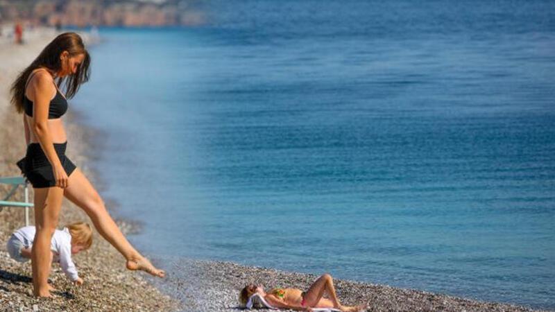 Soğuk hava uyarılarının peş peşe geldiği günlerde Antalya'da turistler denize girdi